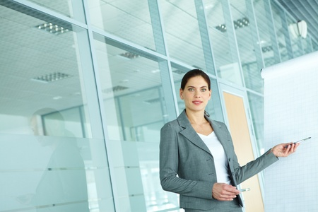 business attire teacher: A beautiful businesswoman pointing at whiteboard and looking at camera Stock Photo