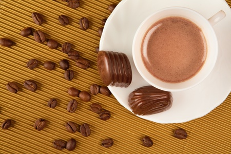 lunch break: Above view of cup of coffee with praline and grains near by