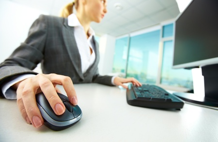 Image of female hands pushing keys of a computer mouse and keyboard photo