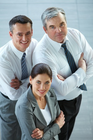A business team with pretty leader in front looking at camera and smiling Stock Photo - 12873274