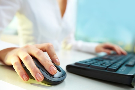 Image of female hands clicking computer mouse photo