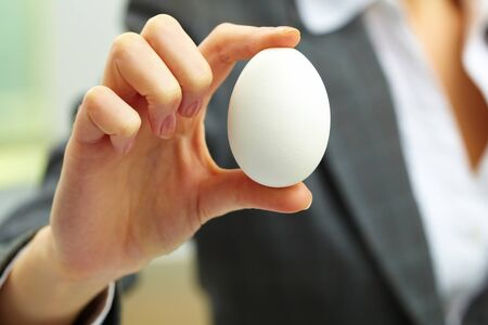 eternal: Close-up of white egg in female hand Stock Photo