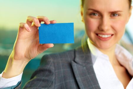 Image of confident businesswoman showing blank visiting card in her hand photo