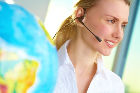 travel agent: Portrait of smiling tour agent with headset consulting client online