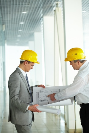 Two architects looking at a project and discussing it photo