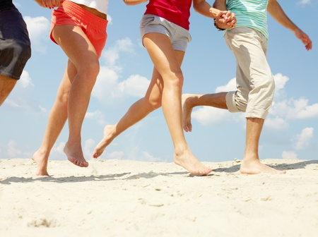 sandy feet: Legs of three friends running on beach in summer  Stock Photo