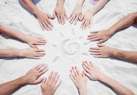 manos unidas: Círculo de manos en la arena con un sol Foto de archivo