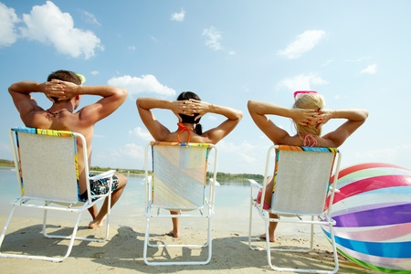 the chaise lounge: Back view of three friends resting in chairs on the beach Stock Photo