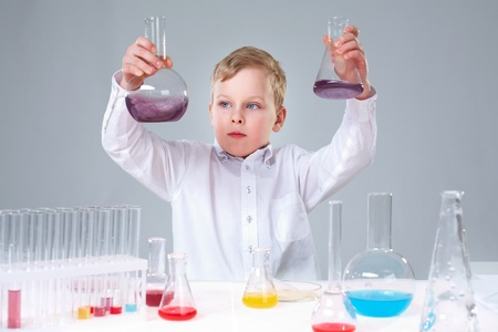 A little boy holding two flasks with liquids and looking at them