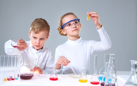 A little boy pouring liquid into a tube and his assistant shaking a flask  photo