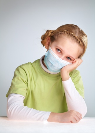 medical mask: A little girl sitting in protective mask