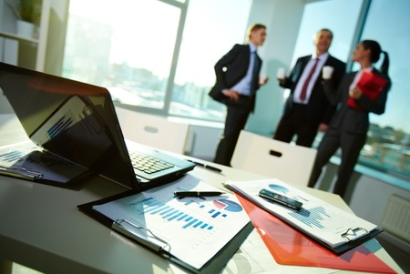 Image of business documents on workplace with three partners interacting on background photo