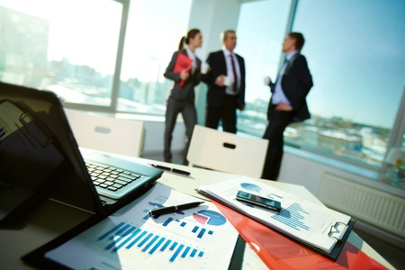 financial item: Image of business documents on workplace with associates talking on background Stock Photo