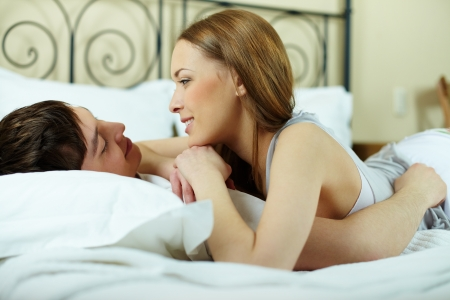 Portrait of young couple lying in bed and looking at one another photo