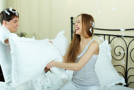 Happy couple playing with pillows in bed photo