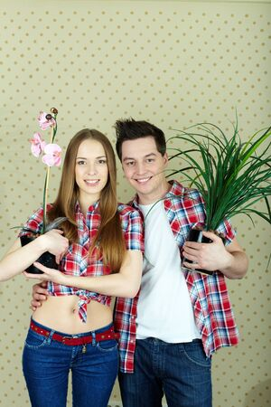 Happy couple with domestic flowers looking at camera  photo