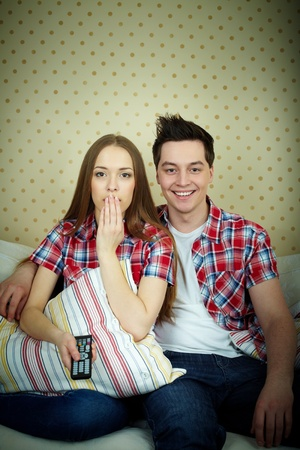 Portrait of young couple during watching TV photo