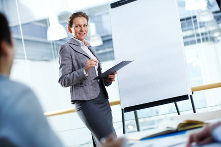 A businesswoman standing by whiteboard and looking at her partners photo