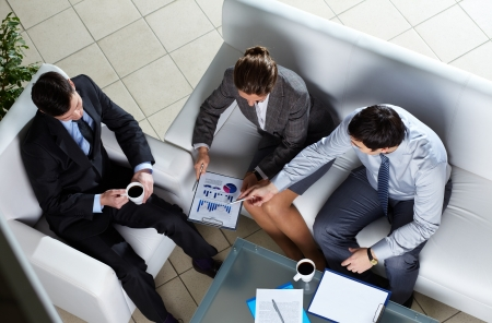 consulting team: Above angle of business group discussing papers Stock Photo