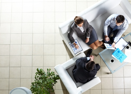 Above angle of three associates interacting at meeting photo