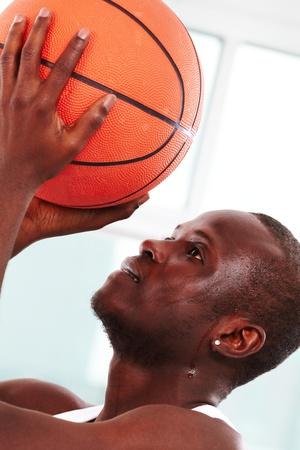 Image of a basketball player throwing ball into basket photo