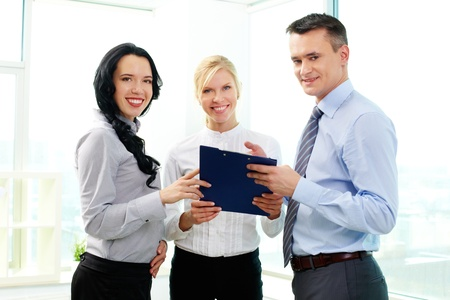 Business people looking at camera while discussing plan Stock Photo - 12873056