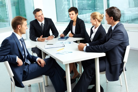 debates: Image of confident colleagues looking at their boss at meeting