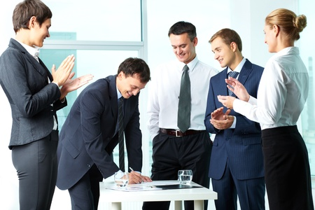Image of co-workers congratulating their colleague while he signing paper at meeting Stock Photo - 12873040
