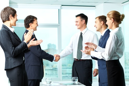 Image of successful co-workers applauding to handshaking men photo
