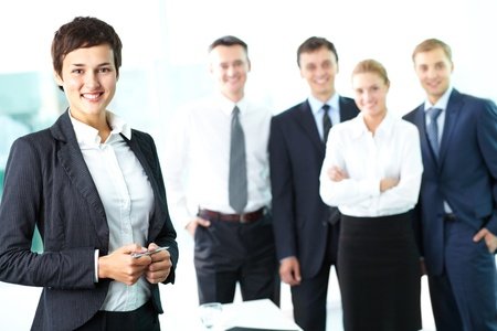 Attractive woman looking at camera and smiling against her business team Stock Photo - 12873091