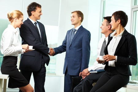 handshaking: Two men handshaking while other business partners looking at them Stock Photo