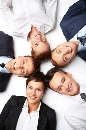 Five business people lying in circle, looking at camera and smiling Stock Photo - 12873019
