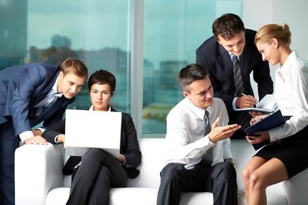 gente comunicandose: Cinco personas de negocios se comunican en la oficina