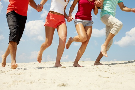 Legs of three friends running on beach in summer  photo