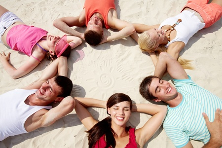 Six friends lying on sand in circle  Stock Photo - 12964027
