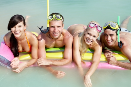 snorkel: Four friends in scubas lying on sand by water Stock Photo