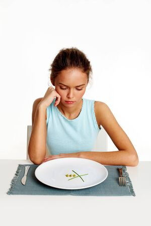 Portrait of sad girl looking at peas and leeks on plate Stock Photo - 12963987