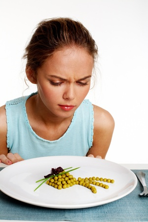 dislike: Portrait of pretty young girl looking at pea starter with dislike