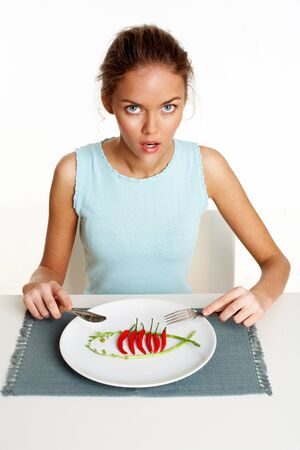 Portrait of pretty young girl with fork and knife in hands and plate with red hot chili peppers in front Stock Photo - 12964005