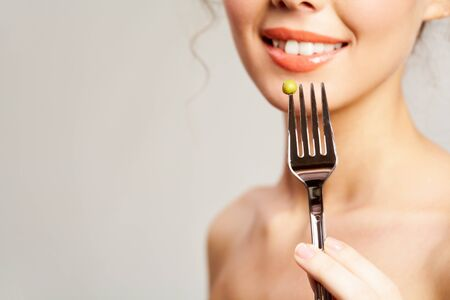 Close-up of fork with pea held by smiling girl photo