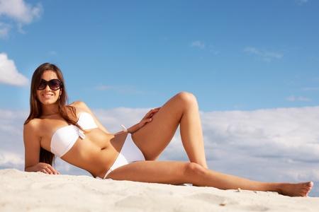 sunbathe: Image of female in white bikini sunbathing on sandy beach