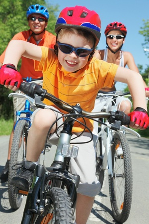 active family: Portrait of happy boy riding bicycle in the park with his parents behind