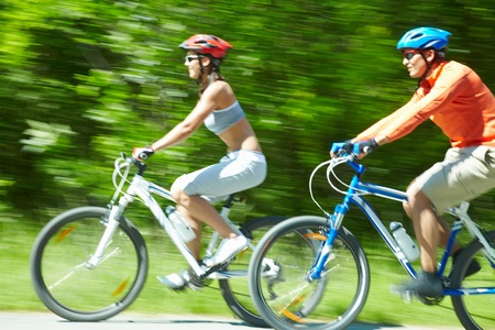 Image in motion of two bicyclists riding on country road photo