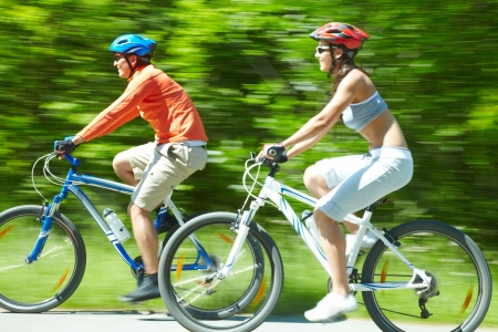 Image in motion of two bicyclists riding down country road photo