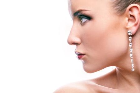 visage: Hermosa mujer con aretes largos en el fondo blanco