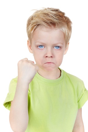 angry blonde: Cute little boy threatening at camera with a fist Stock Photo