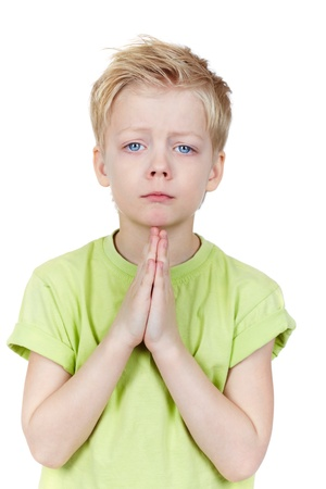 Charming kid putting his hands together as if begging for something