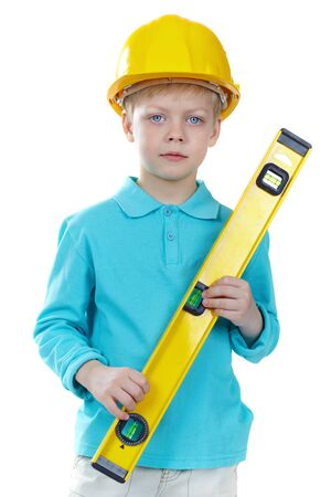 Cute boy in hardhat holding a level and looking at camera Stock Photo - 13036552