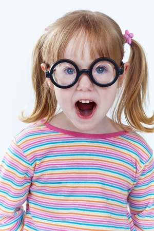 surprised child: Portrait of a girl in funny glasses looking at camera
