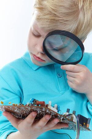 Little blond guy looking at a mother board through magnifying glass Stock Photo - 13037603